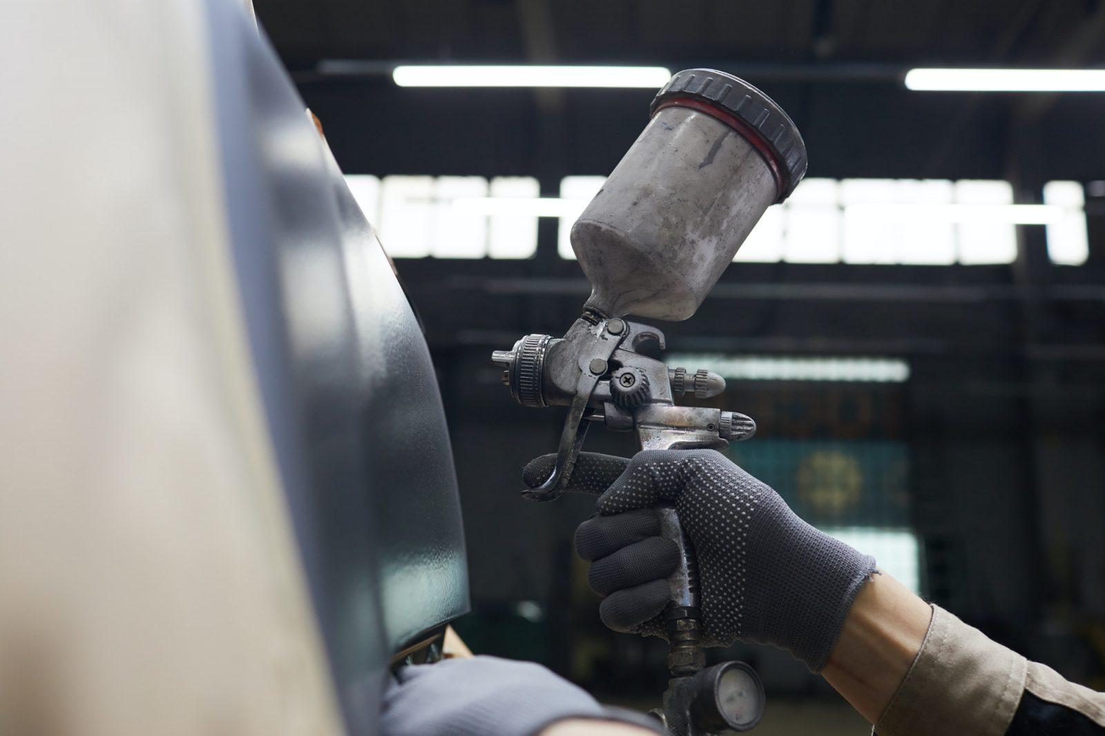 Hand With Spray-gun Painting Car